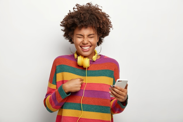Plan demi-longueur d'une femme joyeuse ravie se pointe, tient un téléphone portable, exprime des émotions agréables, porte des boucles d'oreilles, un pull coloré, un casque autour du cou