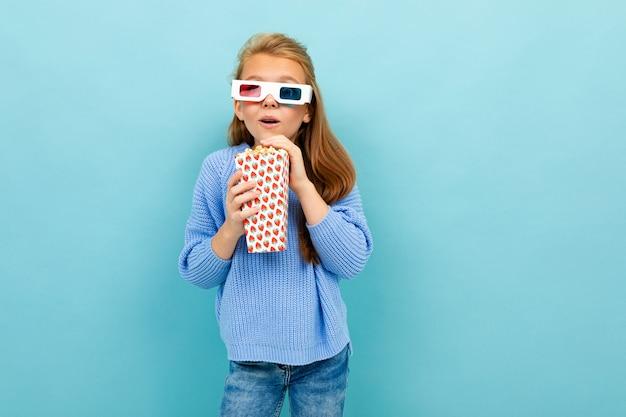 Plan d'une demi-longueur d'une fille élégante joyeuse sur un fond bleu avec des lunettes pour un film 3d et un seau de pop-corn