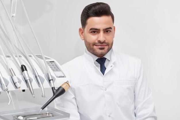 Plan d'un dentiste professionnel hispanique masculin souriant assis à son bureau profession profession stage connaissances dentisterie manteau uniforme travailleur concept d'emploi.