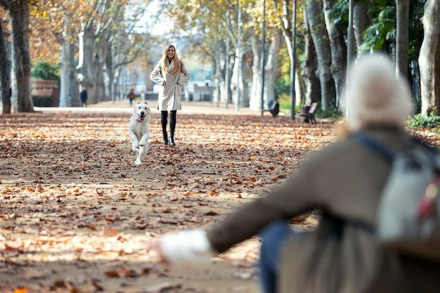 Plan de deux beaux amis marchant dans le parc tout en jouant avec leur chien dans le parc en automne.