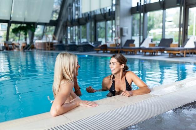 Plan de deux femmes acclamant avec des boissons près d'une piscine. différents cocktails froids rouges, verts et jaunes avec des glaçons, des pailles, un aqua bleu transparent et propre dans la piscine