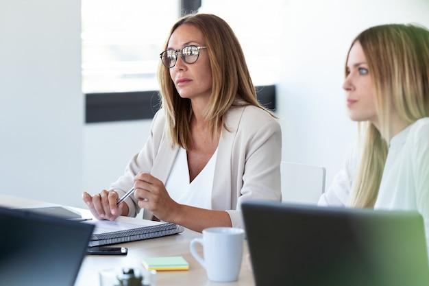 Plan de deux femmes d'affaires concentrées écoutant ses partenaires dans un espace de coworking.