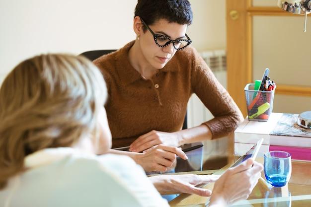 Plan de deux femmes d'affaires parlant de travail et échangeant des idées avec une tablette numérique au bureau.