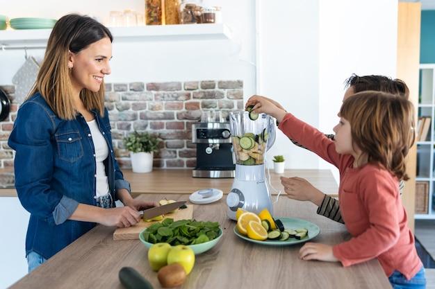 Plan de deux garçons aidant sa mère à préparer un jus détox avec un mixeur dans la cuisine à la maison.