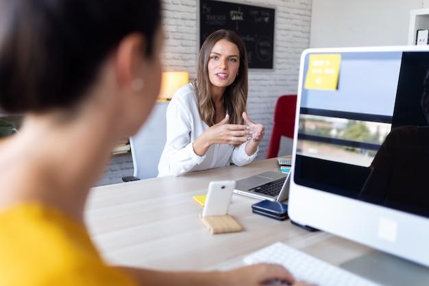 Plan de deux jeunes femmes d'affaires parlant de leur travail en utilisant un ordinateur au bureau.