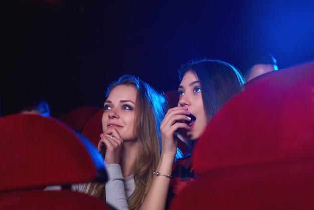 Plan de deux jeunes femmes mangeant du pop-corn en regardant un film intéressant au concept de divertissement du public de style de vie de copyspace de cinéma.