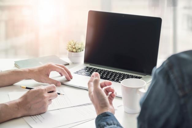 Plan de deux partenaires commerciaux discutant de documents et utilisant un ordinateur portable au bureau.