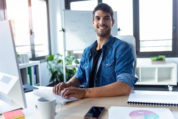 Plan d'un développeur de logiciels regardant la caméra tout en travaillant avec un ordinateur dans le bureau de démarrage moderne.