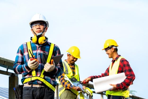 Plan de discussion ingénieur et technicien pour trouver un problème de panneau solaire, ingénieur travaillant sur la vérification et la maintenance dans une centrale solaire, centrale solaire à l'innovation de l'énergie verte pour la vie.