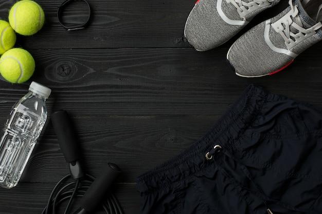Plan d'entraînement avec équipement de fitness sur fond sombre vue de dessus