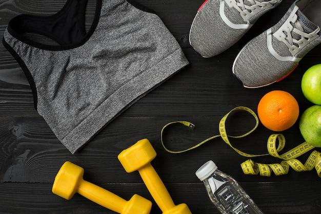 Plan d'entraînement avec nourriture et équipement de fitness sur fond sombre vue de dessus