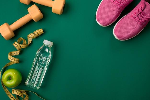 Plan d'entraînement avec nourriture et équipement de fitness sur fond vert vue de dessus