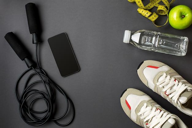 Plan d'entraînement avec nourriture de fitness et équipement de sport sur fond gris, vue de dessus. espace de copie. nature morte à plat