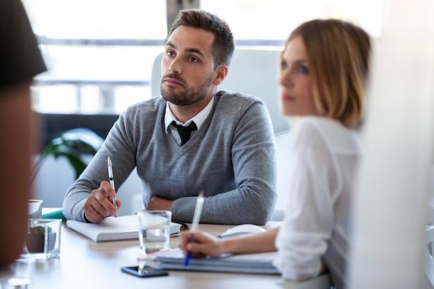 Plan d'une équipe commerciale concentrée écoutant ses partenaires dans un espace de coworking.