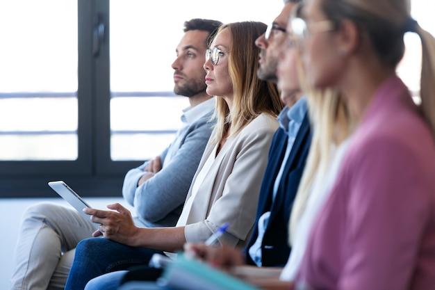 Plan d'une équipe commerciale concentrée prêtant attention à une conférence sur un lieu de coworking.