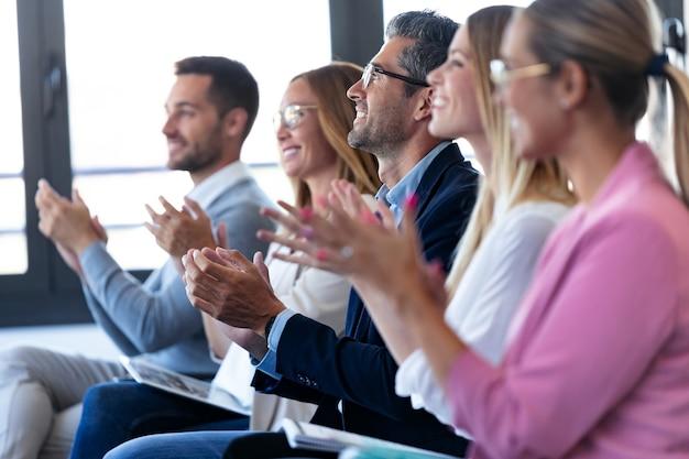 Plan d'une équipe commerciale heureuse applaudissant après avoir écouté la conférence alors qu'il était assis dans un espace de coworking.