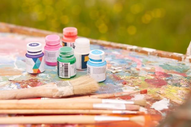 Plan extérieur de divers contenants de peinture et de pinceaux professionnels situés sur une palette sale