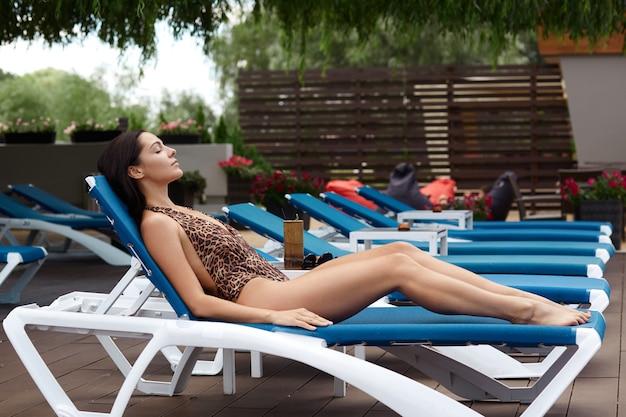 Plan extérieur d'une jeune femme mince allongée sur le salon, une dame qui passe une journée ensoleillée, une jolie femme avec une peau bronzée et un beau corps, portant un maillot de bain, bronzer tout en ayant des vacances d'été tropicales.
