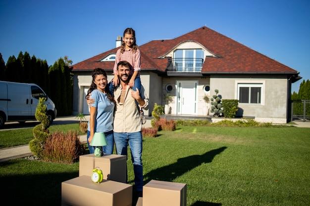 Plan d'une famille debout près de cartons et d'une nouvelle maison prête à emménager.