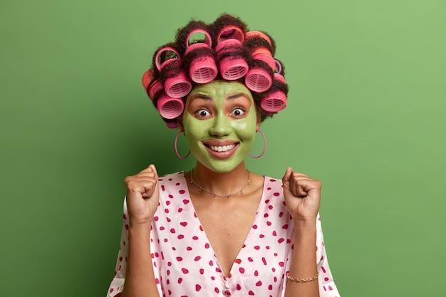 Plan d'une femme adulte joyeuse prévoit que quelque chose de génial se produira, serre les poings avec succès, sourit largement, applique un masque vert hydratant pour les soins de la peau, des rouleaux de cheveux sur la tête, pose à l'intérieur