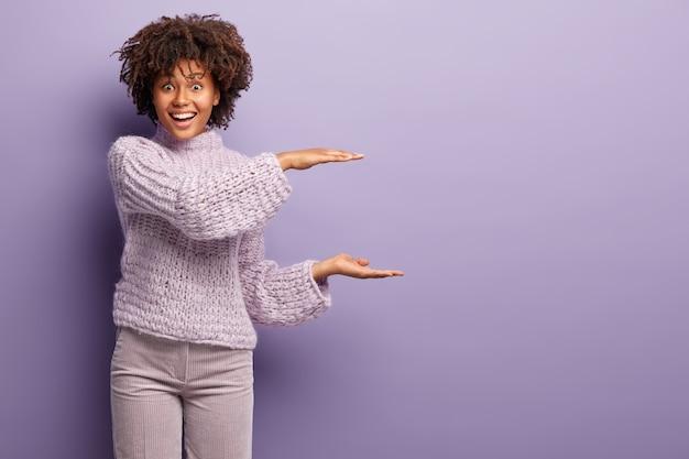 Plan d'une femme afro-américaine heureuse fait un geste de taille, montre quelque chose de grand, a les cheveux bouclés, vêtue d'un pull et d'un pantalon en tricot, isolée sur un mur violet. espace copie maquette