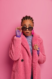 Plan d'une femme afro-américaine surprise regarde des lunettes de soleil avec une expression choquée, ne peut pas en croire ses yeux, habille un manteau d'hiver et des gants de sport, stupéfaite par de grosses réductions dans un centre commercial