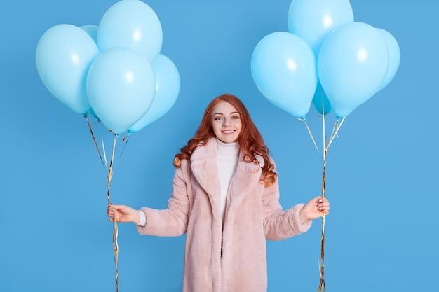 Plan d'une femme aux cheveux rouges joyeuse et joyeuse se sent très heureuse et excitée, passe du temps libre à la fête, porte un manteau de fourrure, pose avec des ballons dans les mains isolées