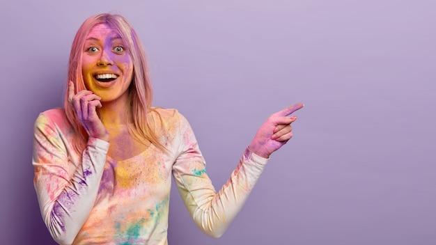 Plan d'une femme blonde heureuse éclaboussée de poudre multicolore, montre l'endroit où se déroule le festival des couleurs holi, exprime des émotions positives, impressionné par les événements festifs en inde, aime le jet coloré