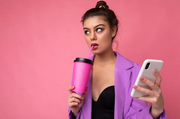 Plan d'une femme brune caucasienne réfléchie tenant du café à emporter vêtue de vêtements décontractés