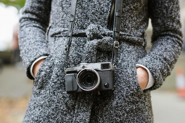Plan d'une femme debout avec ses mains dans ses poches portant un manteau gris et un appareil photo vintage