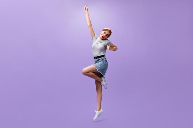 Plan d'une femme en jupe en jean sur fond violet. fille cool mince avec bandana rose et coiffure à la mode en vêtements d'été sautant.