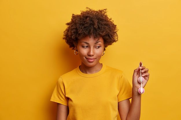 Plan d'une femme à la peau foncée montrant des boules de vagin complétées par une ficelle extensible pour un retrait facile de sa nouvelle collection de jouets sexuels pour le plaisir interne, des inserts dans les zones érogènes pour une sensation supplémentaire