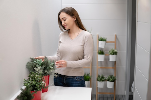 Plan d'une femme qui se soucie des fleurs sur le balcon