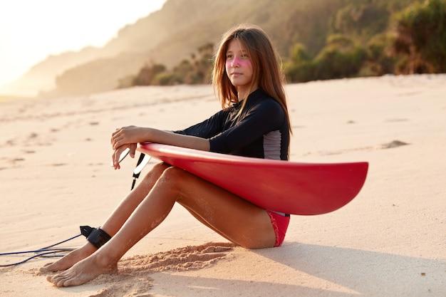 Plan d'une femme séduisante avec une expression réfléchie, a les cheveux longs, regarde au loin sur l'océan ou la mer, vêtue d'une combinaison