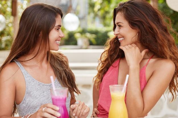 Plan de femmes magnifiques ont des relations amicales, se regardent avec une expression heureuse, se rencontrent dans un restaurant en plein air