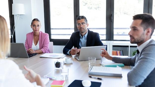Plan de gens d'affaires discutant ensemble dans la salle de conférence lors d'une réunion au bureau.