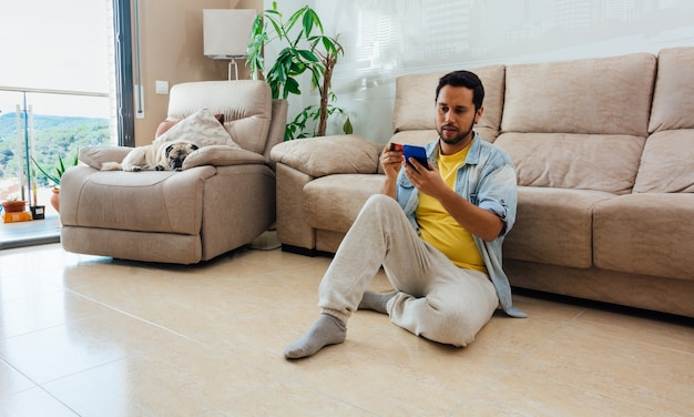 Plan grand format d'un homme assis sur le sol à la maison et à l'aide de son téléphone