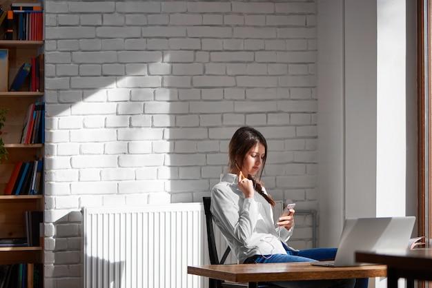 Plan d'une heureuse jeune femme belle assise au café en détournant les yeux en souriant joyeusement en utilisant son copyspace de téléphone intelligent à l'intérieur de la cafétéria du campus étudiant confortable se détendre concept de loisirs