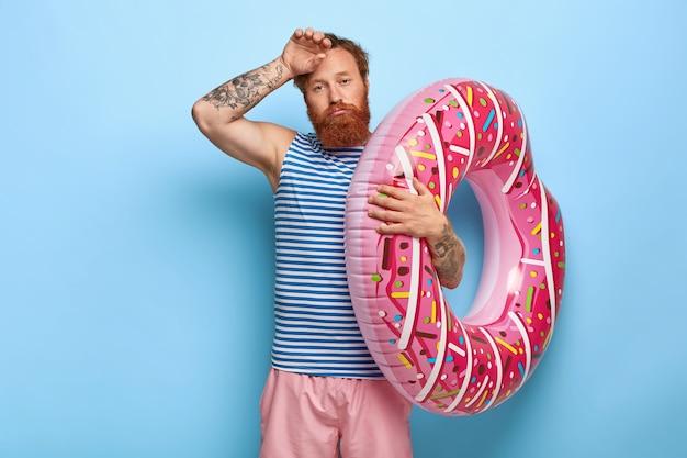 Plan d'un homme aux cheveux roux fatigué posant avec piscine en forme de beignet flottant