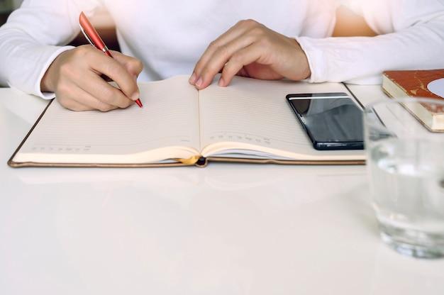 Plan d'un homme en chemise blanche écrivant sur un journal alors qu'il est assis à sa table blanche à la maison