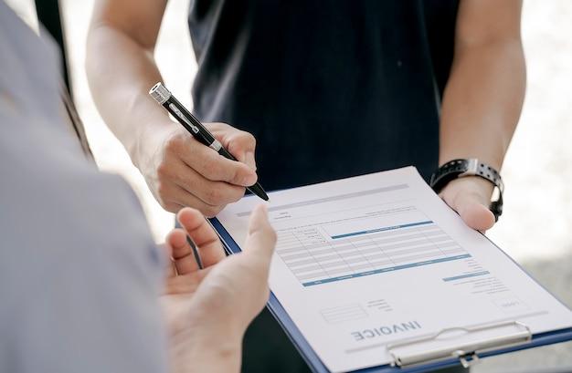 Plan d'un homme qui tient un stylo et signe un contrat.