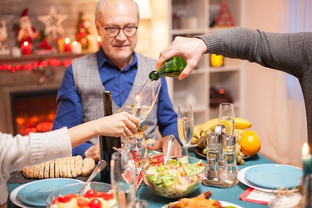 Plan d'un homme versant du vin dans un verre au dîner de noël en famille.
