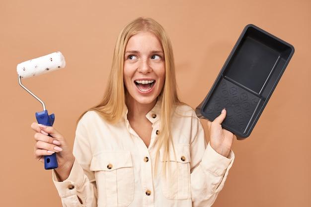 Plan horizontal d'adolescente ravie émotionnelle avec des accolades de dents exprimant l'excitation va peindre les murs dans sa chambre, tenant une brosse et un plateau