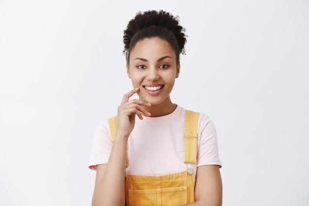 Plan horizontal d'un afro-américain élégant et créatif avec des cheveux peignés en salopette jaune, souriant largement et touchant la joue tout en ayant une excellente suggestion ou un plan, intrigué sur un mur gris