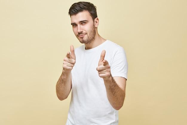 Plan horizontal d'un beau jeune homme charismatique aux cheveux noirs et chaume posant des doigts avant pointés isolés, ayant une expression faciale séduisante confiante, vous choisissant. le langage du corps
