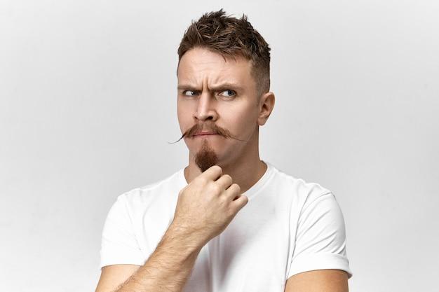 Plan horizontal d'un beau jeune homme vêtu de vêtements décontractés, fronçant les sourcils avec suspicion et caressant sa barbe de goatie, pensant à quelque chose ou élaborant un plan délicat. sentiments et émotions humaines