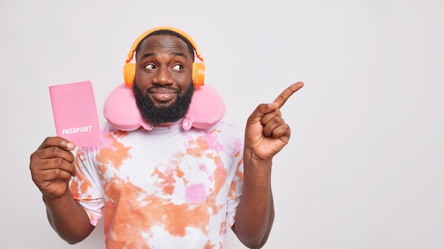 Plan horizontal d'un bel homme barbu a la peau foncée voyage dans les transports détient un passeport utilise un oreiller cervical écoute de la musique via des écouteurs sans fil indique l'éloignement isolé sur un mur blanc