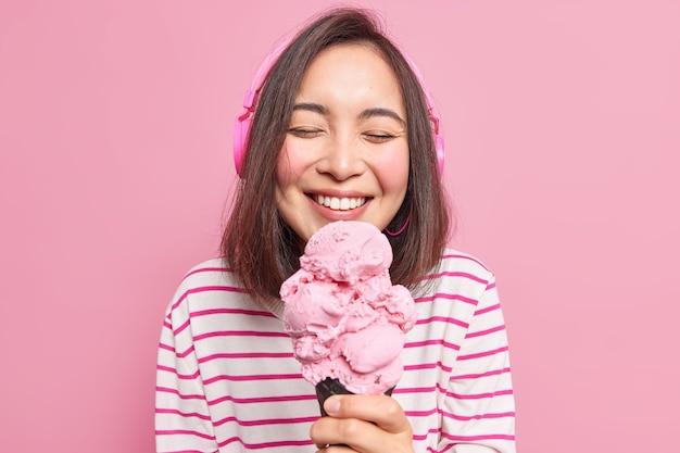 Plan horizontal d'une belle femme asiatique joyeuse du millénaire ferme les yeux du plaisir tout en mangeant une délicieuse crème glacée sucrée aime le dessert d'été écoute de la musique utilise des écouteurs sans fil profite du week-end