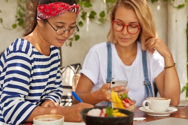 Plan horizontal de belles femmes multiethniques coopèrent ensemble