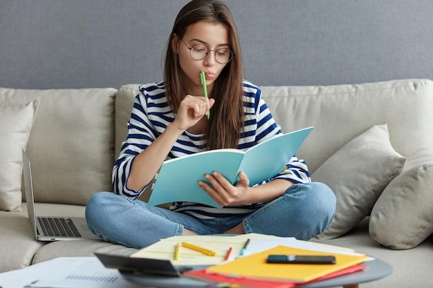 Plan horizontal d'une blogueuse occupée et réfléchie est assise sur un canapé avec un ordinateur portable, tient un stylo près de la bouche
